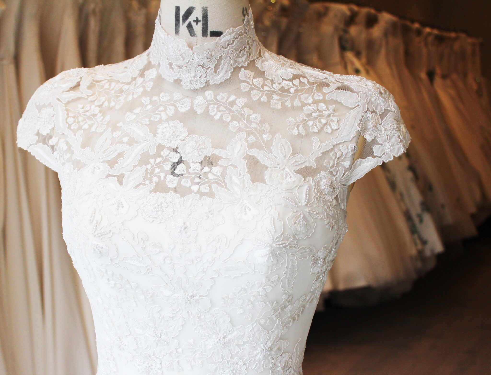 The top of a Phillipa Lepley high neck embroidered wedding gown with cap sleeves.